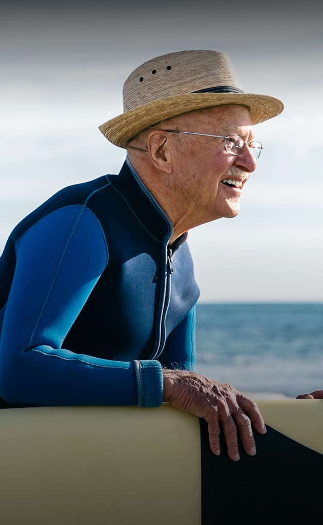 Senior citizen man with surfboard