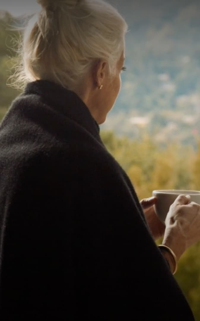 Senior woman looking at the view and drinking coffee