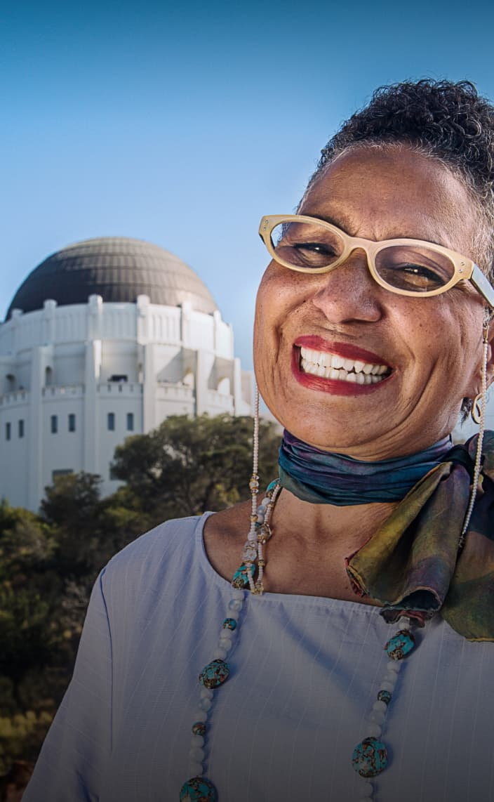 Woman smiling in front of the Griffith Observatory